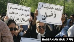 Iranian women brandish banners calling for the improvement of women's rights during a protest in Tehran. File photo.