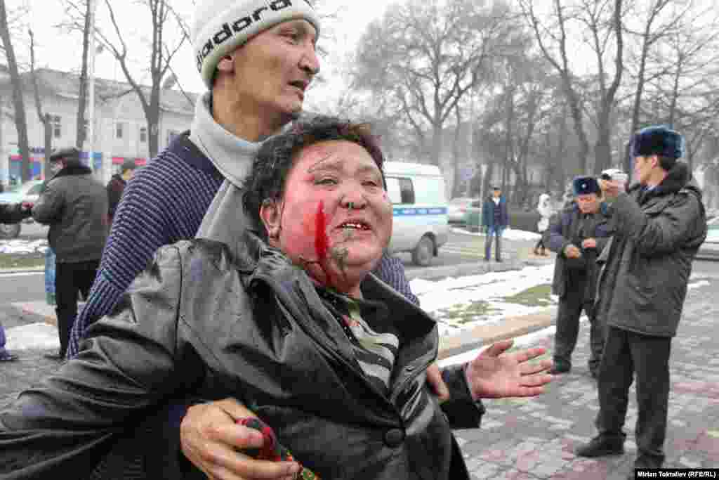 A Kyrgyz woman, Zhyparkan Omurova, tries to commit self-immolation in front of the parliament building in Bishkek to protest a court judgment against her son. (RFE/RL/Mirlan Toktaliev)