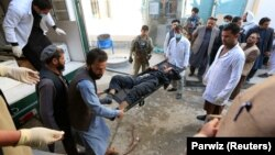 Afghan men carry a victim of the attack in Jalalabad on March 6.