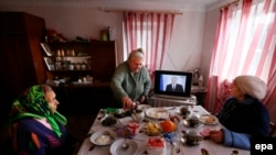 Women have their lunch as they watch Russian President Vladimir Putin on the television addressing the country's Federal Assembly on the Crimean referendum to reunify with Russia outside the peninsula's capital Simferopol.