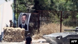 Syria -- A portrait of President Bashar al-Assad is hung on a fence at an army checkpoint at the entrance of the northern town of Jisr al-Shughur, 20Jun2011