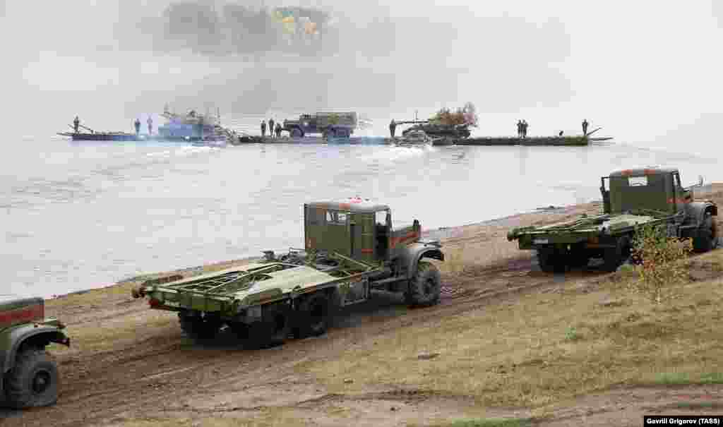Vehicles, including self-propelled artillery being floated across the Tom River on a section of a pontoon bridge.