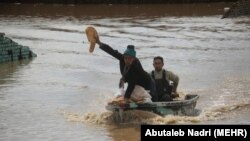 A motorboat carrying volunteers in Aq Qala in northern Iran during flood. A man is showing others he is bringing bread. March 27, 2019