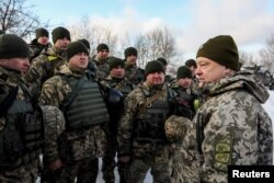 Ukrainian President Petro Poroshenko meets with soldiers during a visit to a defense post located on the contact line with Russia-backed separatists in eastern Ukraine near the rebel-held town of Horlivka in December.
