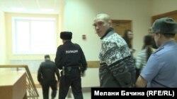 Блогера Вадима Тюменцева ведут в зал суда, где его судят за публикацию видеоролика в Интернете, в котором он критикует военное вмешательство России в Украине.