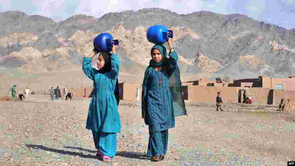 Internally displaced women in Afghanistan carry gas cylinders on their heads on the outskirts of Herat. (AFP/Aref Karimi)