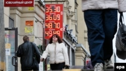 Люди идут рядом с обменным пунктом в Санкт-Петербурге.