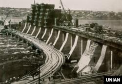 Репродукція архівного фото, на якому зображено греблю ДніпроГЕС (Дніпровська гідроелектростанція) – вид з лівого берега, в середу, 2 вересня 1931 року