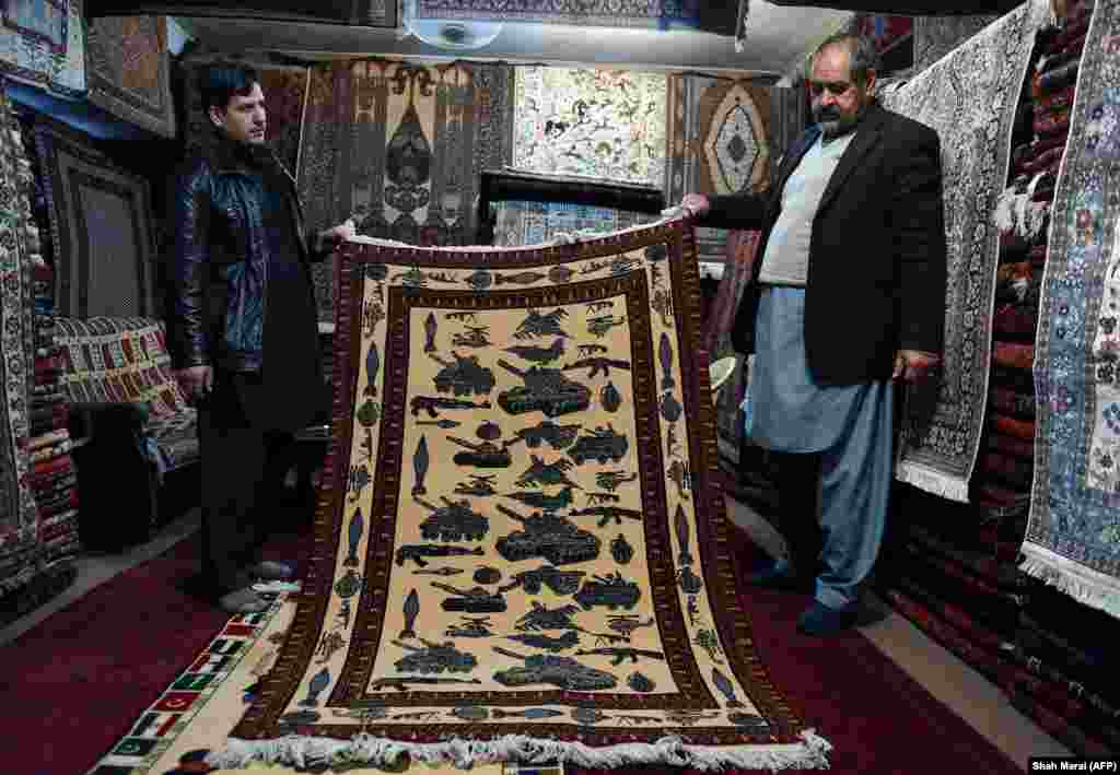"Merchants display a rug decorated with modern weaponry for sale in Kabul in 2015. The same year this photo was made, a carpet seller told AP: ""if fighting stops maybe this custom [of making war-themed rugs] will change [and] people will design something else instead of these weapons and guns; they might start designing [rugs with] flowers and other things."""