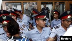 """Полицейские встали в ряд между подсудимыми и их родственниками в день оглашения приговора суда по делу """"о беспорядках в Жанаозене"""". Актау, 4 июня 2012 года."""
