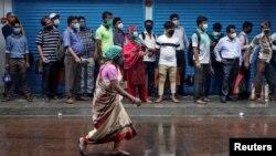 Пассажиры в масках ждут в очереди к посадке в автобус. Индия, август 2020 года.