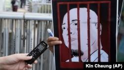 Honq Konqda jurnalist çinli fəal Wu Gan-ın fotosu olan plakata diktofon uzadır, 27 dekabr, 2017-ci il