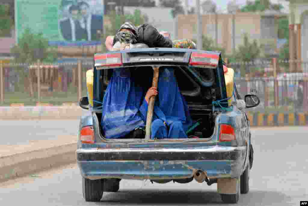 Polio vaccination volunteers ride in the open trunk of a car as they travel to administer the vaccine during a campaign in Afghanistan's Balkh Province. (AFP/Farshad Usyan)