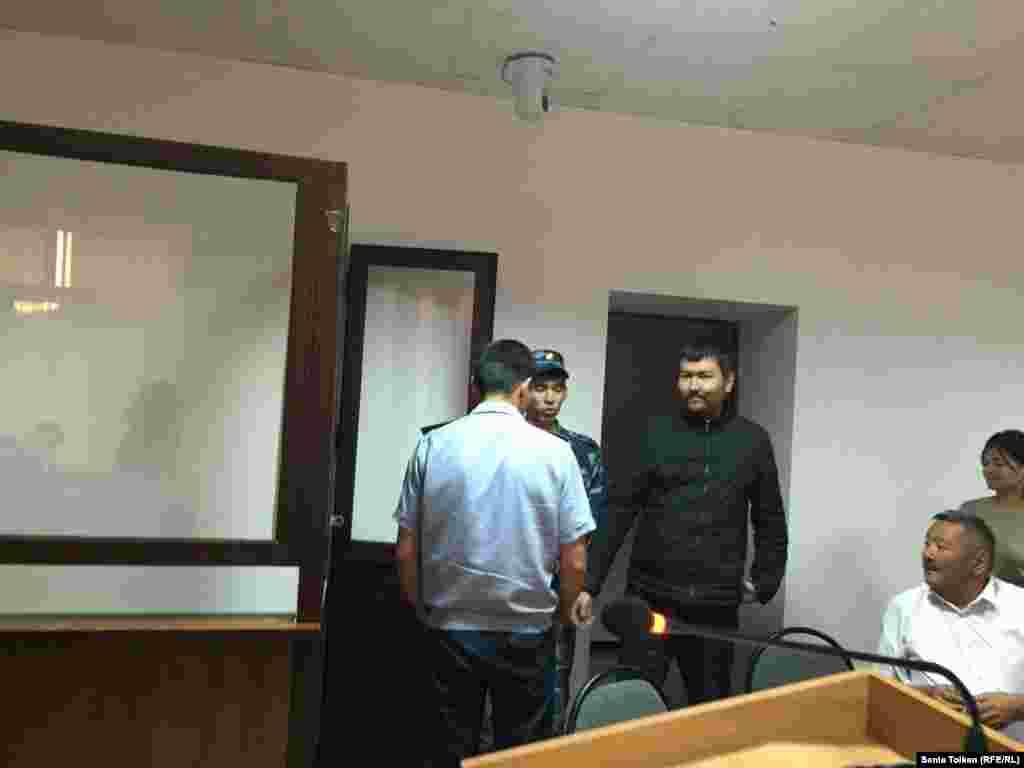 Находящегося под стражей гражданского активиста Талгата Аяна полицейские доставили в зал суда.