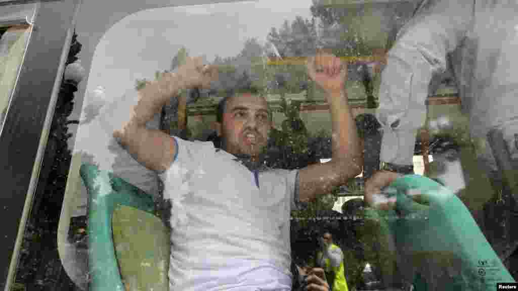 A detained Azerbaijani opposition supporter shouts inside a police bus during an antigovernment protest in central Baku on May 21 just before the Eurovision Song Contest  was due to be held in the city. (Reuters/David Mdzinarishvili)