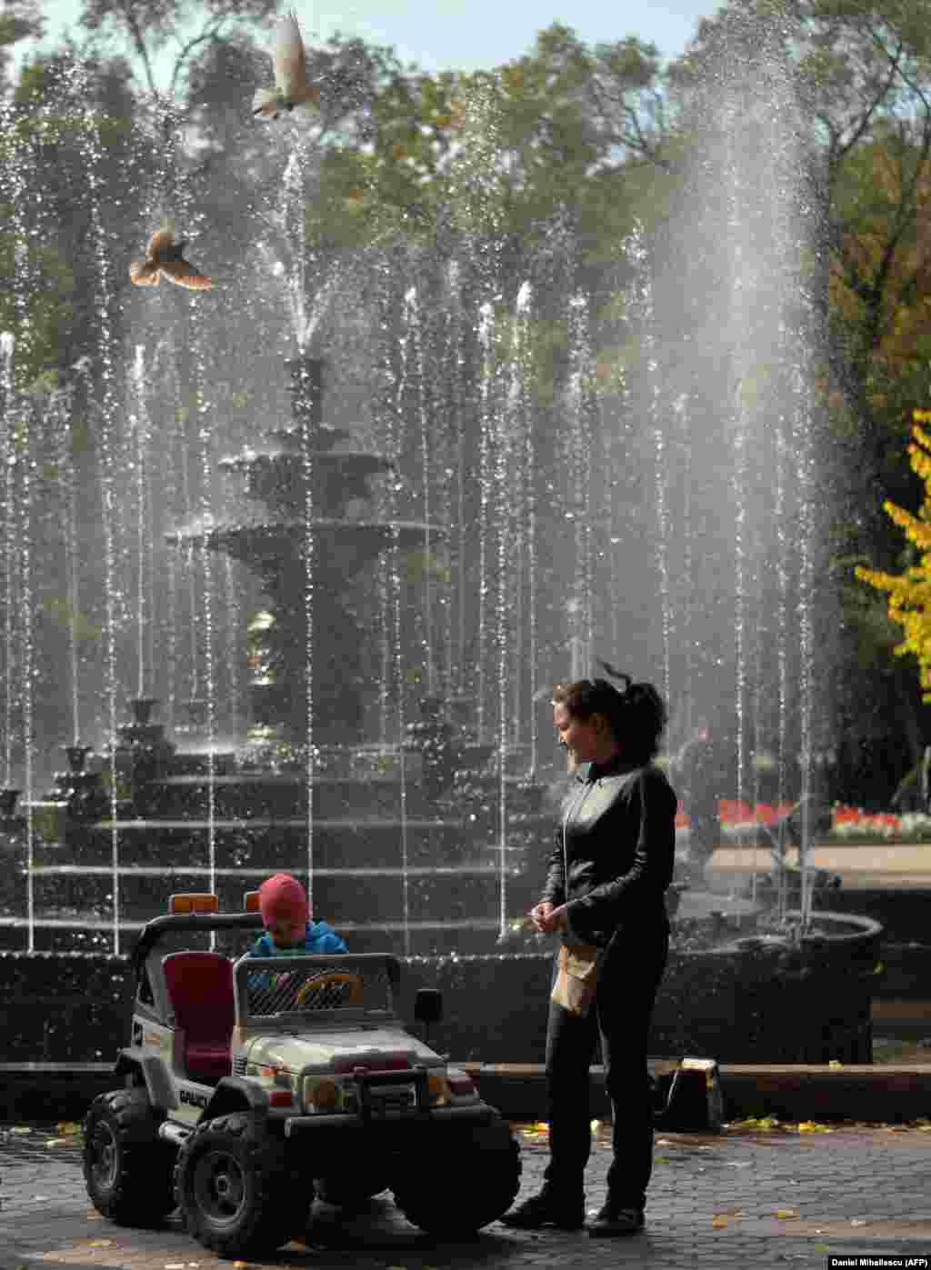 A child plays near a fountain in a downtown park.