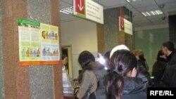 Люди стоят в очереди к консультанту в одном из отделений банков Алматы.