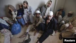 Students wear chains around their ankles while sitting with their belongings at a police station after being rescued during a late-night raid on December 12-13 at the Zakariya madrasah on the outskirts of Karachi.