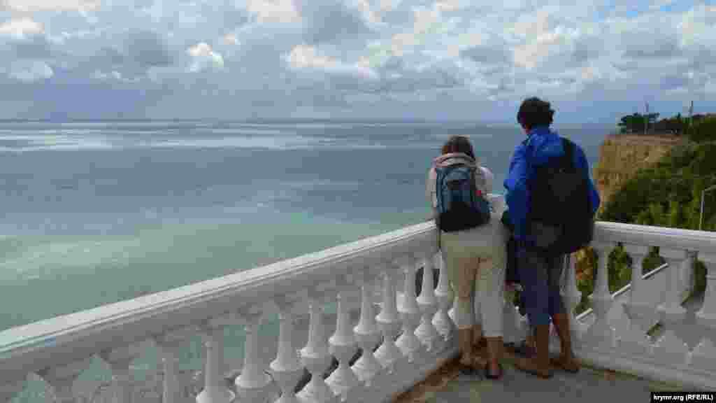 Туристы наблюдают за штормом со смотровой площадки. Из-за пронизывающего ветра они одеты не по-летнему