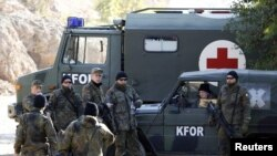 KFOR soldiers from Germany stand by their vehicles in the village of Jagnjenica near the town of Zubin Potok.