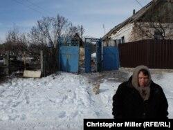 Жительница Авдеевки рядом со своим разрушенным домом