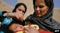 An Afghan woman holds a child as a health worker administers a polio vaccine. Polio-eradication can be dangerous work in some parts of Afghanistan, because some religious extremists have condemned it.