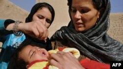 Дәрігер әйел полиомиелитке қарсы вакцинаны баланың аузына тамызып тұр. Ауғанстан, Кабул, 16 қараша 2009 жыл.