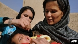 An Afghan woman holds a child as a health worker administers the polio vaccine. The WHO says that large-scale immunization can stop an outbreak.