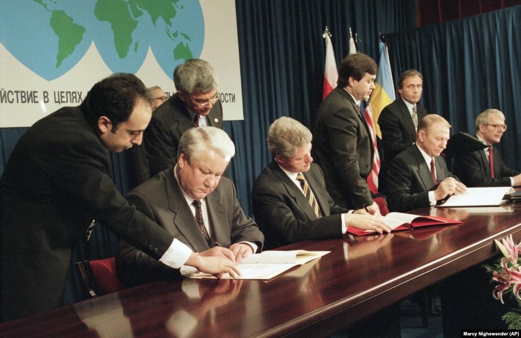 Президент России Борис Ельцин (слева), президент США Билл Клинтон (в центре), президент Украины Леонид Кучма и премьер-министр Великобритании Джон Мейджор (справа) на церемонии подписания Украиной Договора о нераспространении ядерного оружия – в Будапеште 5 декабря 1994 года. Соглашение официально носит название Будапештского меморандума и требует от России соблюдать территориальную целостность Украины