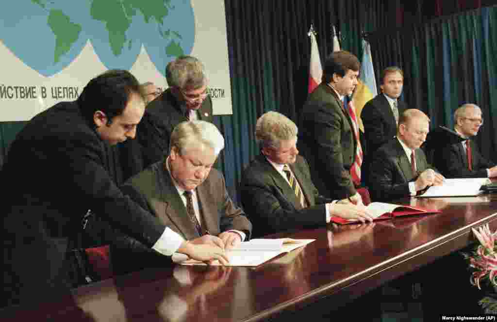 Russian President Boris Yeltsin (left), U.S. President Bill Clinton (center), Ukrainian President Leonid Kuchma, and British Prime Minister John Major (right), sign the Nuclear Nonproliferation Treaty in Budapest, Hungary, on December 5, 1994. Known as the Budapest Memorandum, the agreement officially dismantled Ukraine's nuclear arsenal.