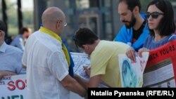 Перехожі підписують листівку до дня народження Сенцова