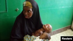 A Somalian woman holds a malnourished baby in Banadir hospital in Mogadishu.