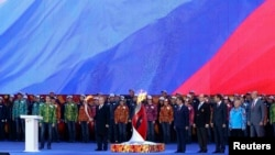 Russian President Vladimir Putin (center) holds a lit Olympic torch during a ceremony to mark the start of the Sochi 2014 Winter Olympic torch relay in Moscow on October 6. The flame fared more poorly at the Kremlin.