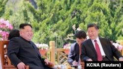 شی جین پینگ (راست) حین ملاقات با رهبر کوریای شمالی کیم جونگ اون