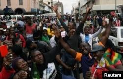 Роберт Мугабені әскерилер биліктен ығыстырғаны туралы хабарға шаттанып жатқан адамдар. Хараре, 18 қараша 2017 жыл.