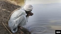 A man drinks contaminated water from a stream in the Cholistan Desert, near Bahawalpur, Pakistan.