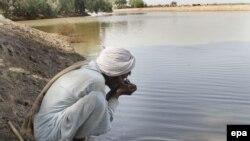 Čovek pije kontaminiranu vodu iz reke u pustinji Kolistan u Pakistanu