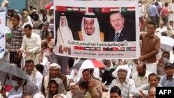 مخالفان حوثیها، پلاکاردی با تصاویر رئیسجمهوری ترکیه، پادشاه عربستان و امیر قطر در دست دارند (تعز آوریل ۲۰۱۵)