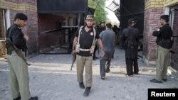 Полициячылар Банну түрмөсүнө жасалган чабуулда зыян тарткан дарбазанын жанында турушат. 15-апрель 2012