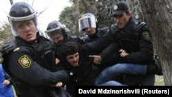 Police detain a man who was protesting in solidarity with Ismayilli residents after a riot in Baku on January 26.