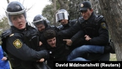 Police officers detain a man at a protest in Baku in January 2013.