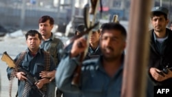 Afghan security personnel work at the scene of an attack in Kabul in May.
