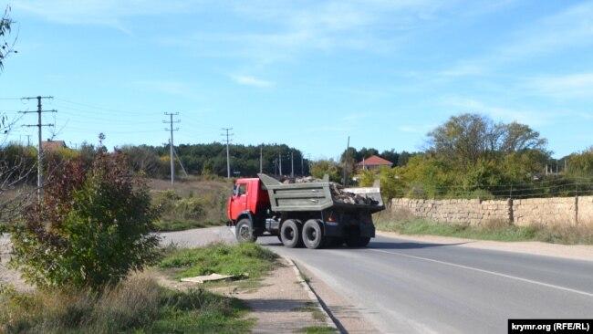 КамАЗ со строительными отходами сворачивает с Монастырского шоссе в Юхарину балку