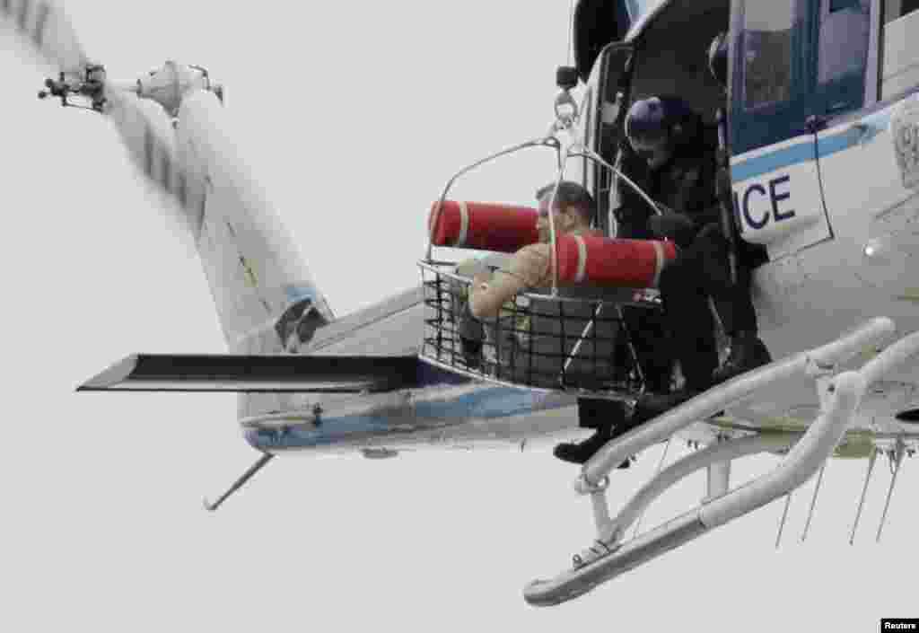 """В середине сентября 2013 года в штаб-квартире ВМС США в """"Вашингтон Нейви-Ярд"""" бывший работник базы 34-летний Аарон Алексис открыл стрельбу по военным. Он убил 12 человек, 8 получили тяжелые ранения. Сам Алексис был убит во время часовой перестрелки с полицией. На фото – полицейский вертолет эвакуирует одного из военных с базы."""