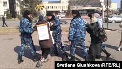 Наразылық танытқан астаналық тұрғын Алтын Червалиеваны полиция ұстап әкетіп барады. Астана, 3 сәуір 2014 жыл.