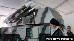 "Iranian Supreme Leader Ayatollah Ali Khamenei is seen near a ""3 Khordad"" system which is said to had been used to shoot down a U.S. military drone, undated"