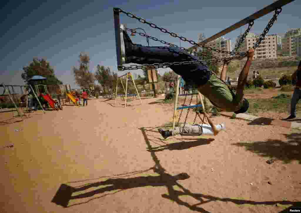 Palestinian protesters swing as they rest at a park during clashes with Israeli troops at a protest in support of Palestinian prisoners on hunger strike in Israeli jails, near the Jewish settlement of Beit El in the West Bank. (Reuters/Mohamad Torokman)