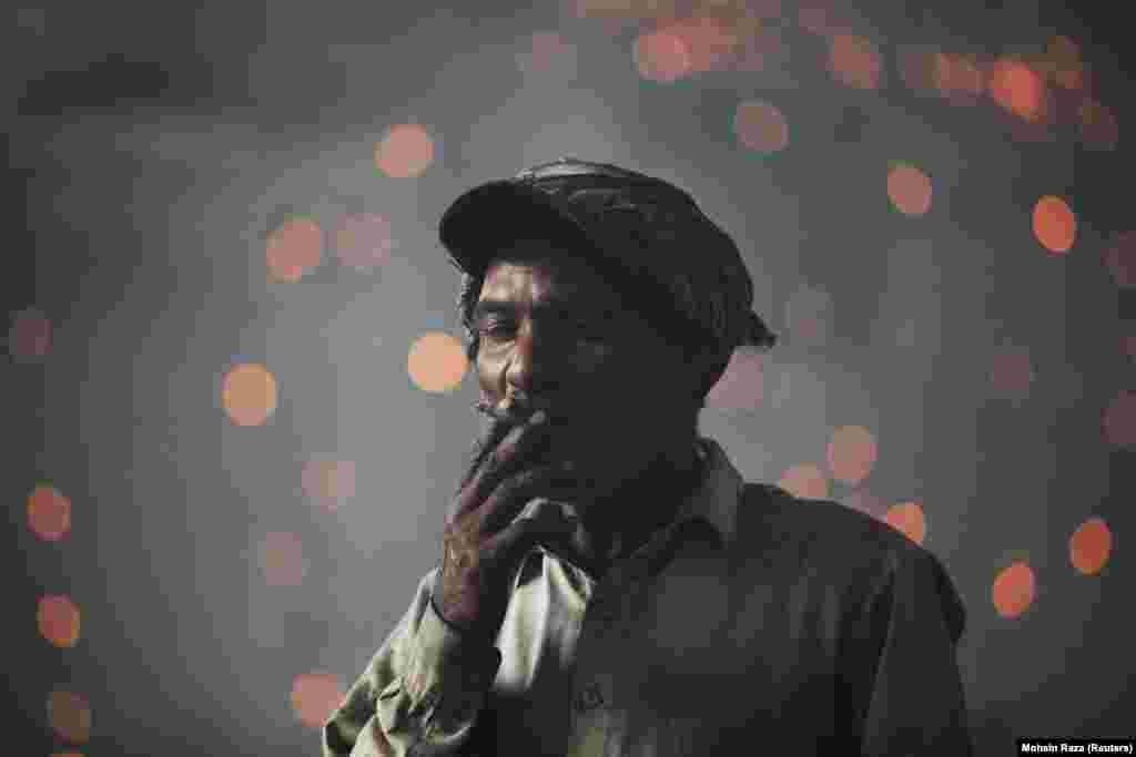 A Pakistani laborer smokes a cigarette as he takes a break from working in a foundry in Lahore. (Reuters/Mohsin Raza)