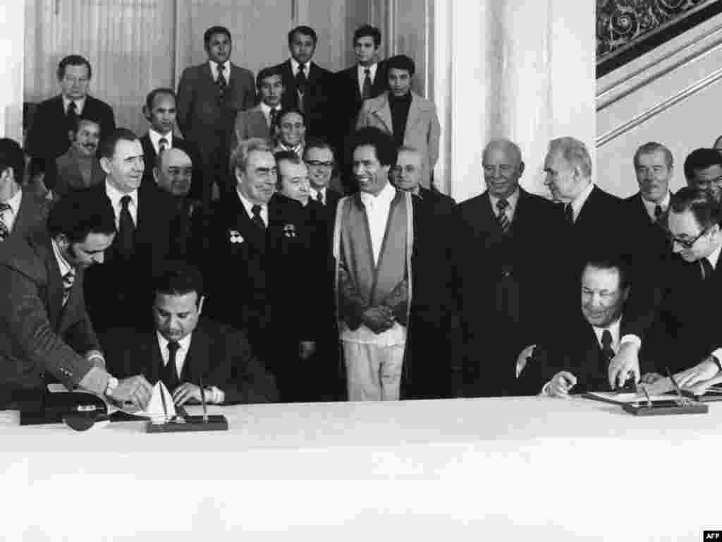 Qaddafi (center) and Soviet leader Leonid Brezhnev (to Qaddafi's right) smile as members of their delegations sign agreements during a visit to Moscow in December 1976.