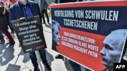 "Activists display placards in front of the Chancellery in Berlin in April during a demonstration calling on Russian President Vladimir Putin to put an end to the persecution of gay men in Chechnya. The protesters called on German Chancellor Angela Merkel, who met with Putin in Sochi on May 2, to raise the issue. She said afterward that she had urged Putin to ""use his influence"" to end the abuse."